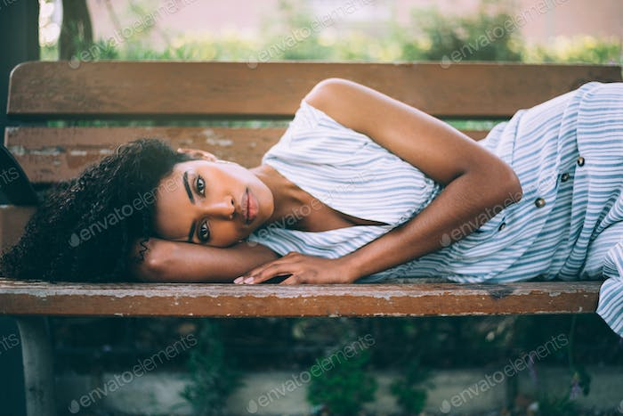 Beautiful young black woman laying down on a chair in a park
