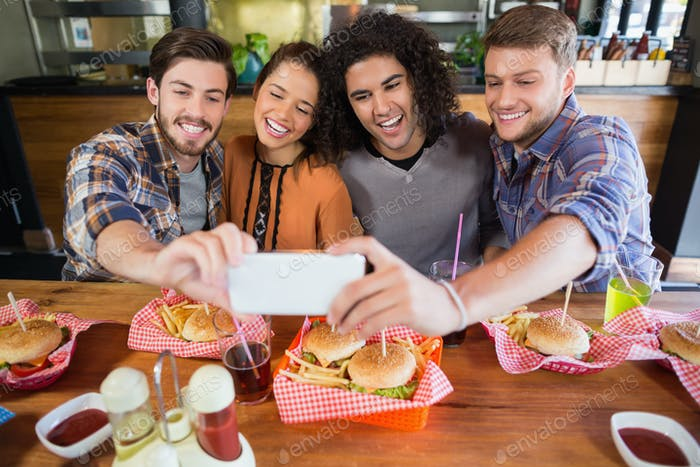 Cheerful friends taking selfie in restaurant