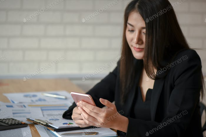 Young asian female executives use mobile phone in the office.