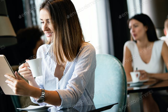 Happy young woman drinking tea and using tablet computer