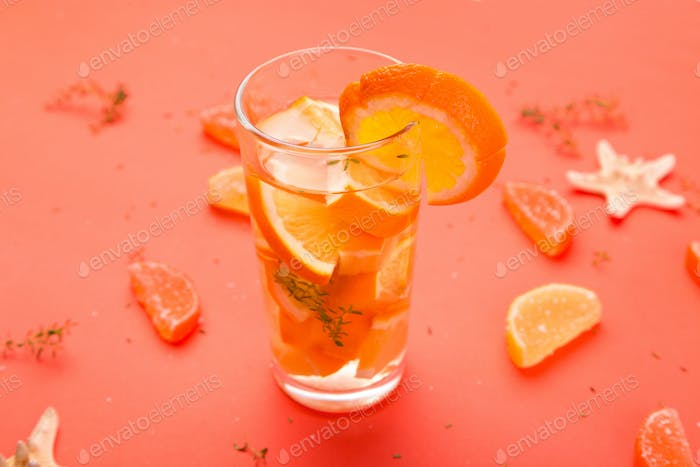 Orange fruit cocktail, detox water on orange background.