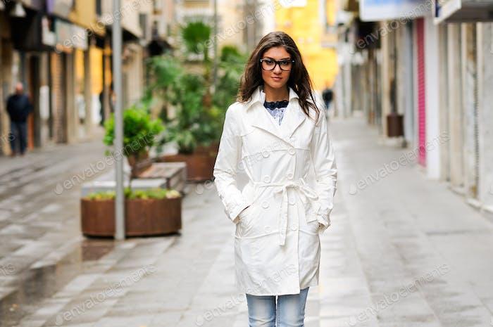 Beautiful woman with eyesglasses walking in urban background