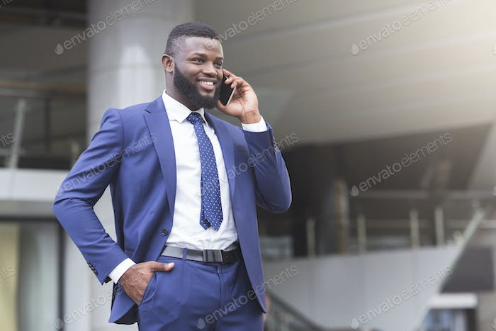 Young attractive businessman making phone call and smiling