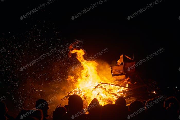 Gente viendo un gran fuego en la noche