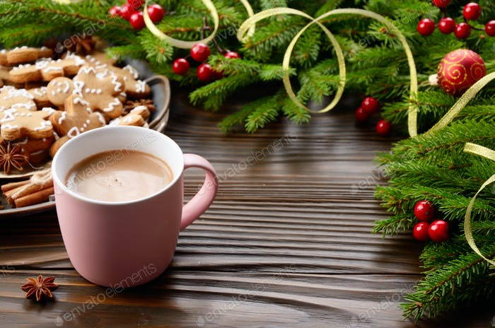 Christmas background of pink mug with hot chocolate, spruce branch and tray