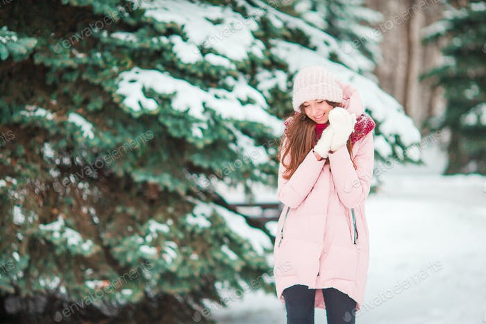 Portrait of beautiful woman smiling outdoors on beautiful winter snowy day in forest