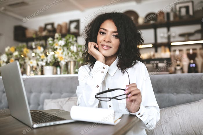 Nice African American girl working in restaurant with laptop and notebook