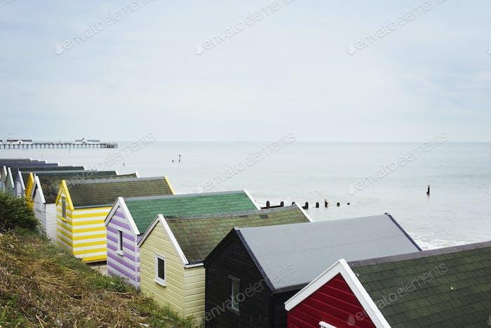 Row of colourful huts on a sandy beach under a cloudy sky.