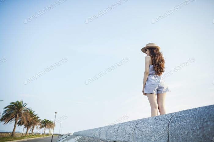 A young woman in summer clothes standing by a road looking into the distance.