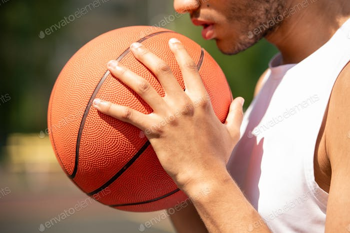 Young contemporary male basketball player holding ball by his face and chest