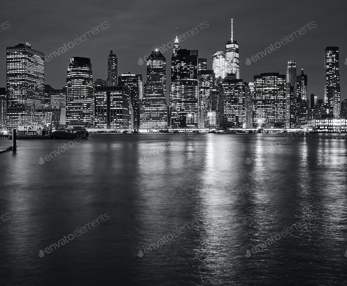 New York City Skyline spiegelt sich in East River in der Nacht, USA.