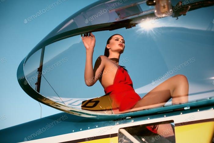 Mode-Modell Mädchen als Pilot in einem roten Kleid sitzt eine Kabine Propellerflugzeug während des Sonnenuntergangs