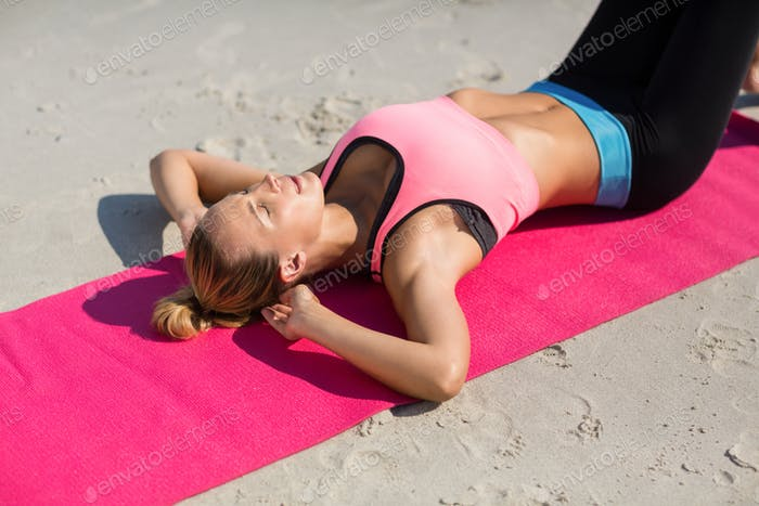 High angle view of young woman exercising on exercise mat