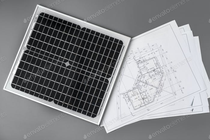 Architectural blueprints and solar panel on table