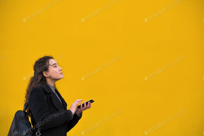 An Asian girl in a black coat and a phone with her hand walks