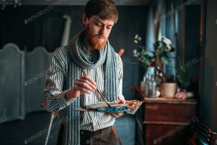 Künstler malt Farben auf der Palette, Kunststudio