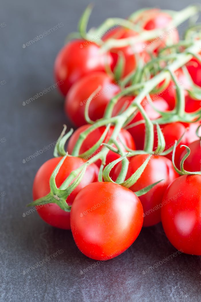 Bunch of cherry tomatoes on dark slate background, vertical
