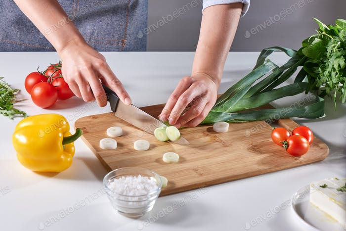 Fresh leek slices cut into the hands of a female cook on a wooden board on the kitchen table around