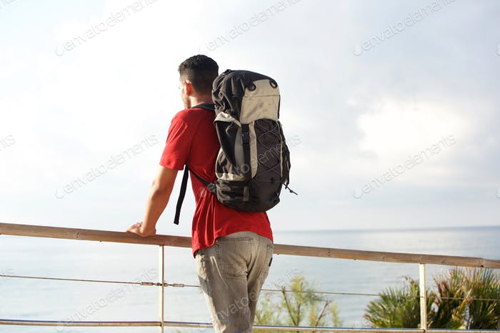 male backpacker looking at the sea