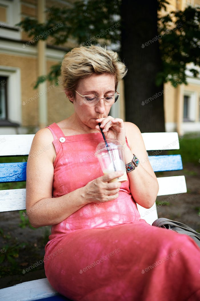 Adult woman using smartphone on bench