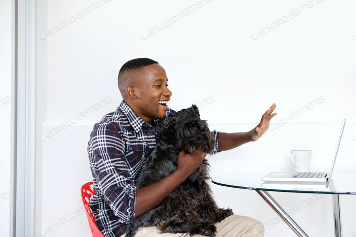 Young guy with a dog waving while video chatting on laptop