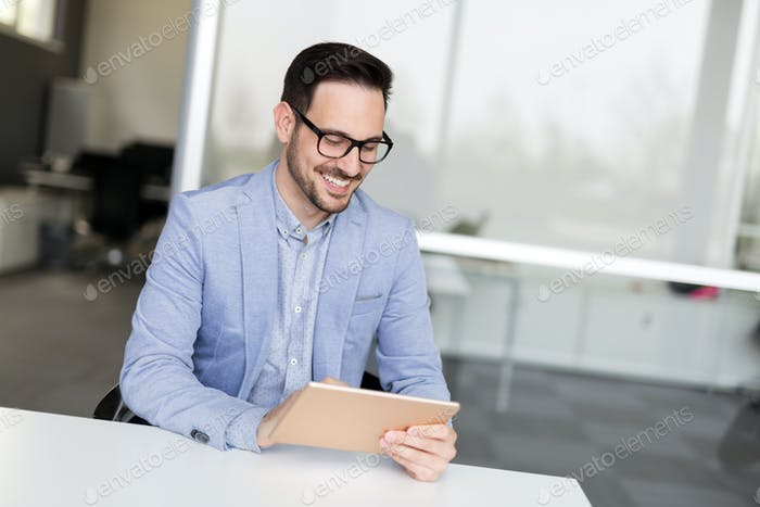 Portrait of handsome successful businessman holding tablet