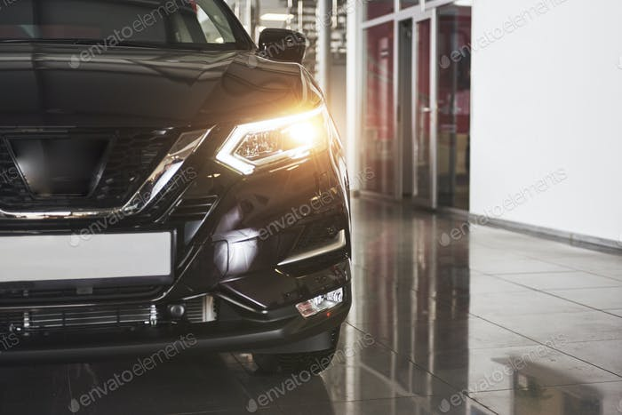 The headlights and the hood of a black luxury car