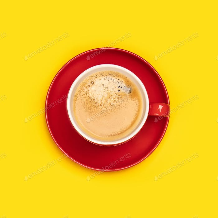 Red cup of coffee on yellow background