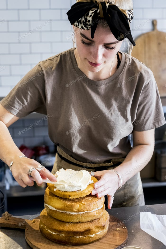 A cook working in a commercial kitchen assembling a layered sponge cake with fresh cream.