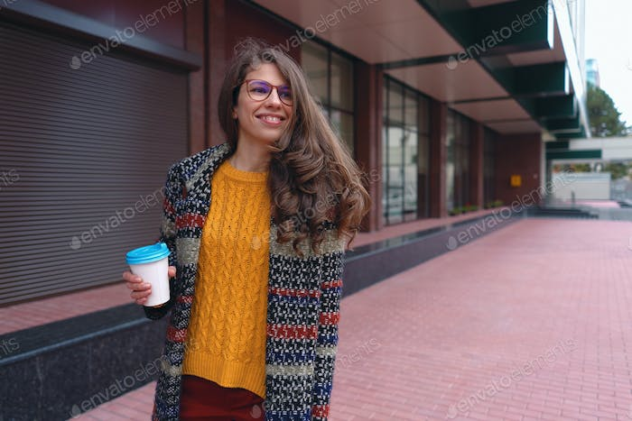 young woman in coat drinking coffee outdoors.