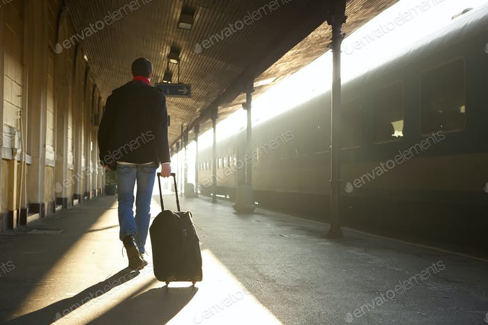 Mann Reisen mit Tasche am Bahnhof