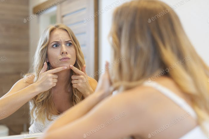 Angry woman squeezing  pimple from face