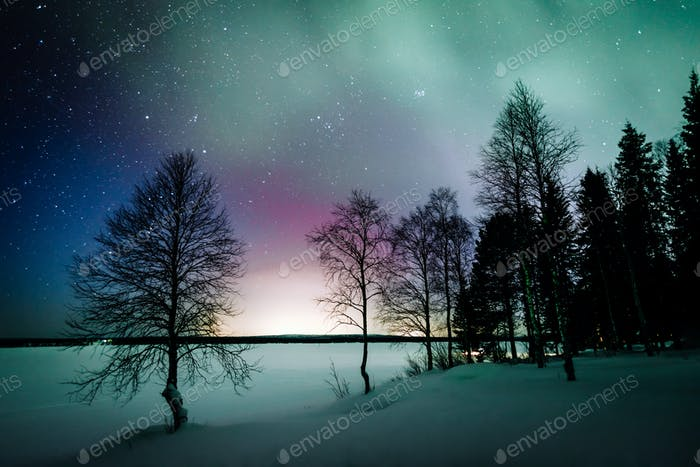 Northern lights Aurora Borealis activity over the lake in winter Finland