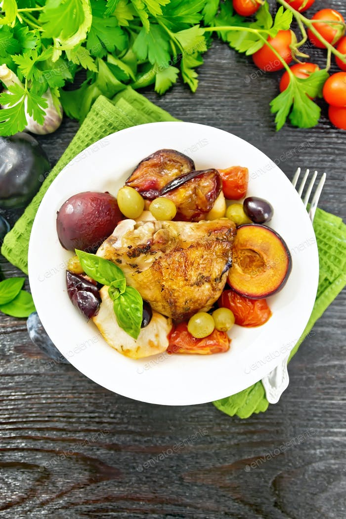 Chicken with fruits and tomatoes in plate on dark board top