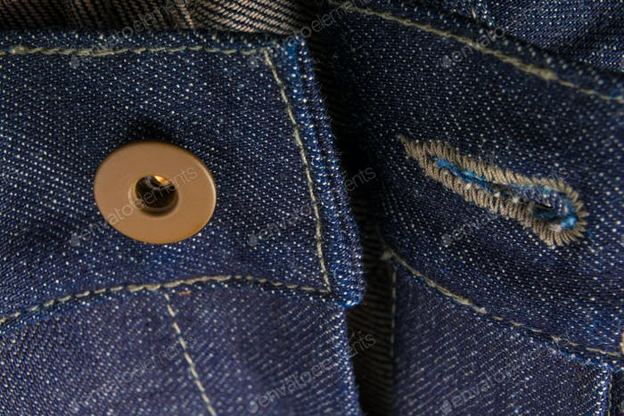 Close up of jeans fragment with open button. Denim texture.
