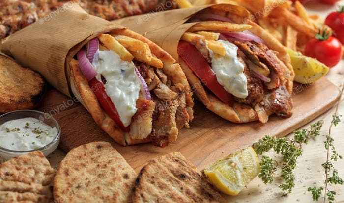 Greek gyros wrapped in pita breads on a wooden table