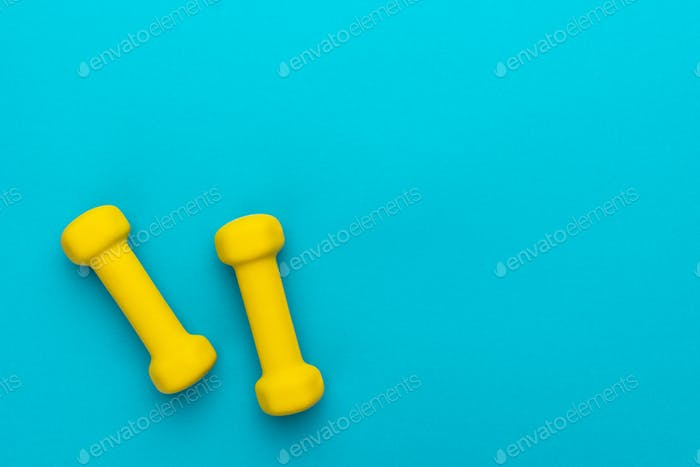 Flat Lay Photo Of Yellow Fitness Dumbells Over Blue Backgound With Copy Space