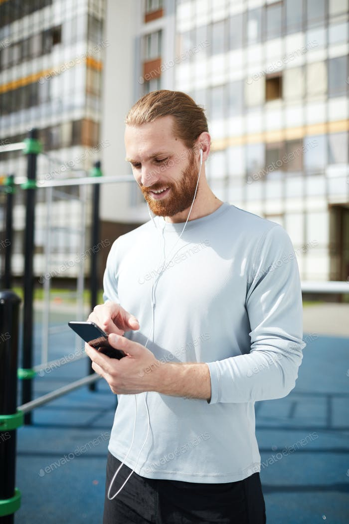 Happy man using smartphone on training ground