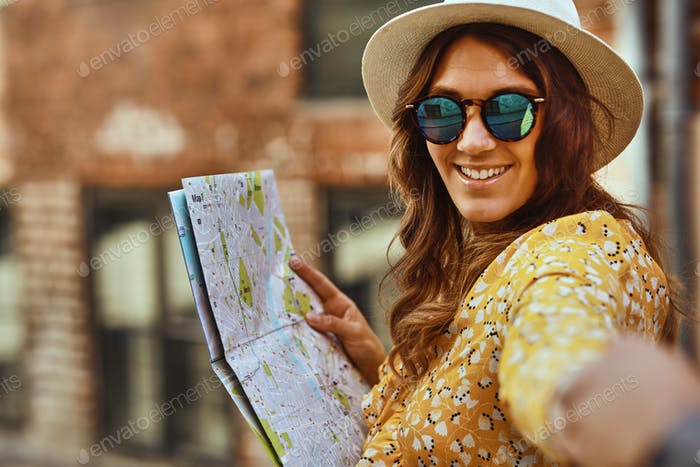 Smiling woman with a map leading someone through city streets