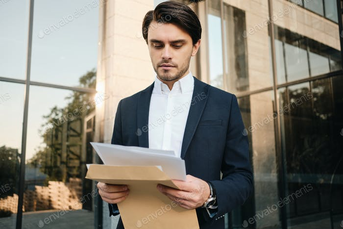 Young businessman opening envelope with documents outdoors with glass building on background