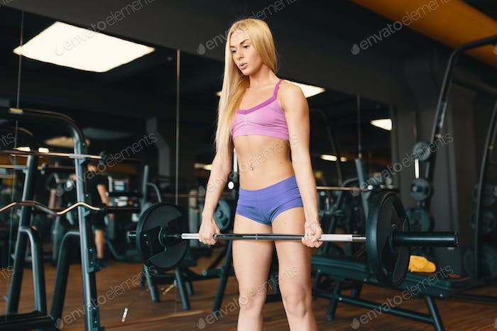 Blond Sportswoman in mini shorts lifting barbell at gym workout