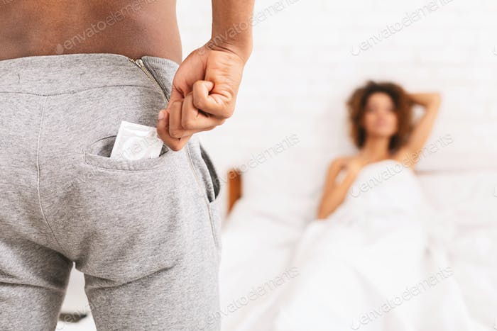 African man taking condom from pants, naked woman waiting in bed