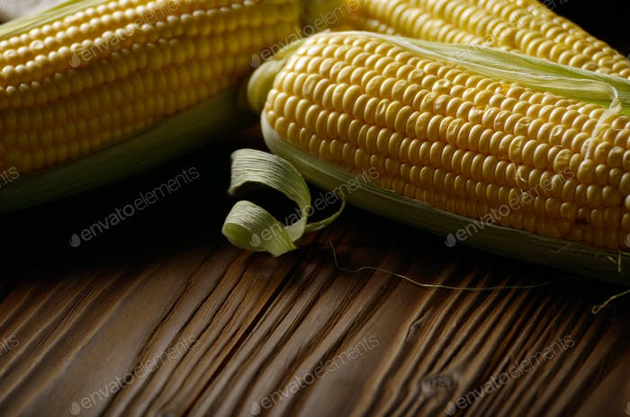 Reife frische Bio-Maiskolben auf Holztisch