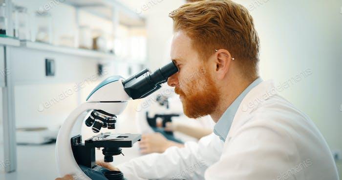 Nachwuchswissenschaftler im Labor durch das Mikroskop