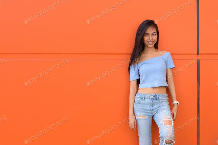 Young happy Asian teenage girl smiling while leaning against orange painted wall