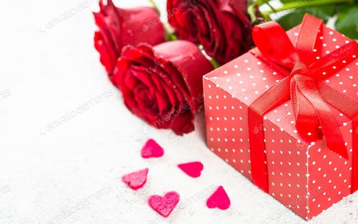 Valentinstag Hintergrund. Rote Rosen, Herzen und Geschenk auf weiß