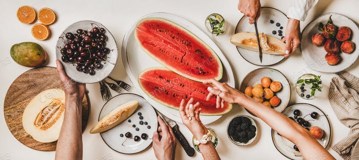 Flat-lay of peoples hands with fruits, berries and lemonade
