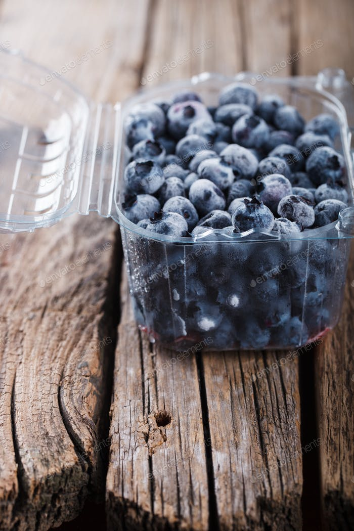 Blueberries frozen in a plastic container.