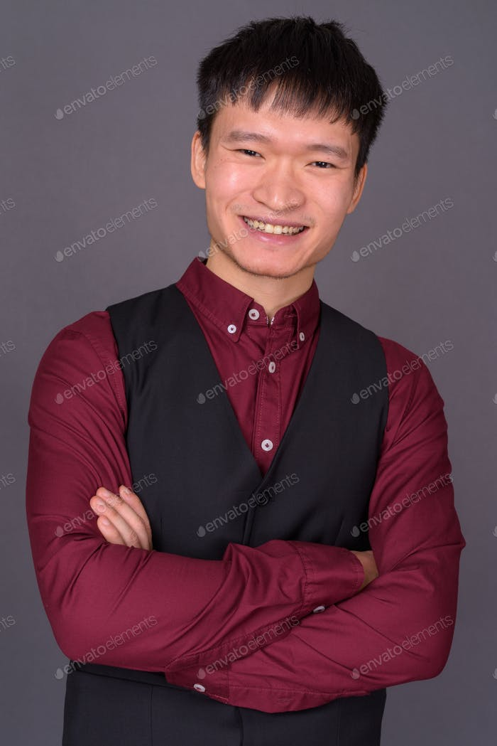 Portrait of young Chinese businessman against gray background