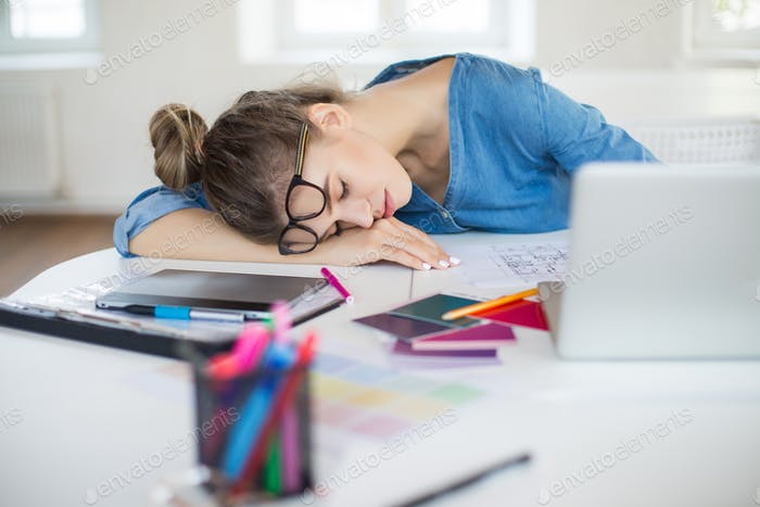 Young tired woman with eyeglasses on head sleeping on desk with